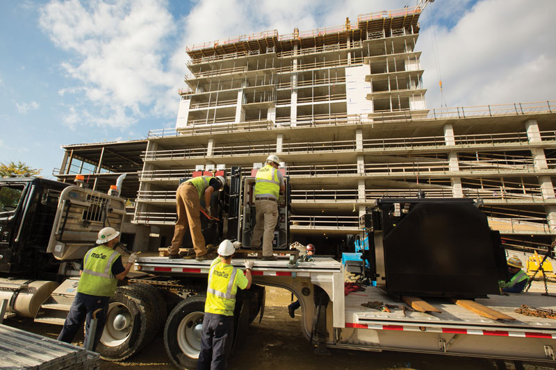 MGE crews unload a large electric transformer to help power a new high-rise development with 244 apartments.