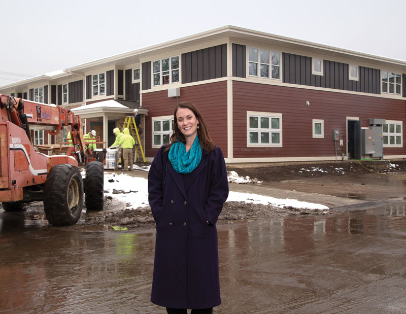 Karla Thennes, Executive Director of Porchlight, stands in front of a new development with 16 efficiency apartments to provide people with supportive, permanent housing. The MGE Foundation donated to the capital campaign and to help Porchlight fulfill its mission to decrease the homeless population.