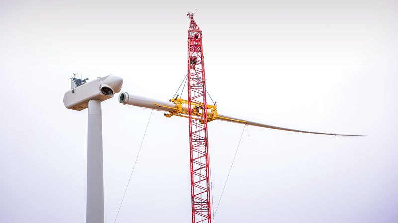 A crane places a blade on the hub of one of MGE's 33 Vestas turbines at the company's new Saratoga Wind Farm in northeast Iowa. The tips of the blades at Saratoga reach nearly 500 feet high in the air