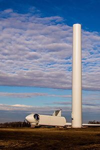 A rotor and nacelle rest next to one of Saratoga's towers.